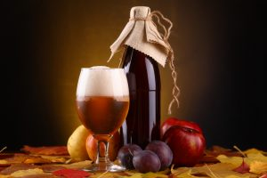 Bottle and glass of beer surrounded by fruit
